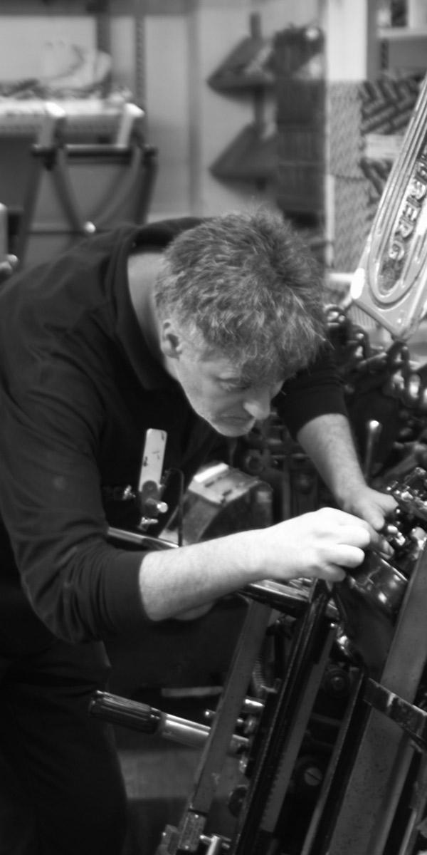 Raúl ajustando los engranajes de una máquina.